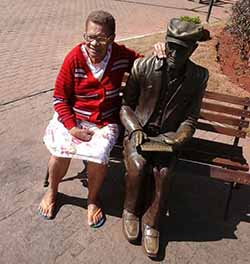 Dona Tereza ao lado da estátua de Chico Xavier